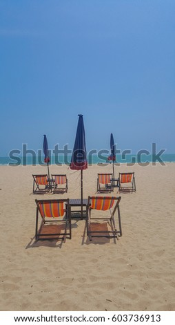 Armchairs with umbrellas beside the beach is symbol of holiday in summer to closed the sea.