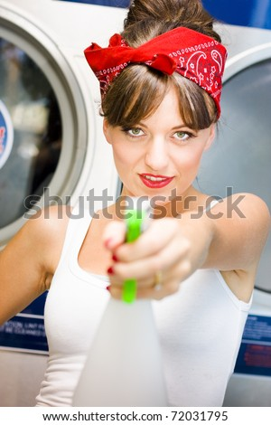 Armed And Dangerous An Attractive Female Cleaning Lady Points A Bottle Of Disinfectant Cleaner While Smiling In A License To Clean Conceptual - stock photo