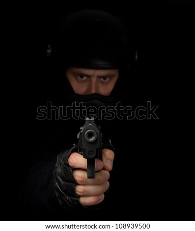 Armed assassin with motorcycle helmet aiming into the camera against a black background - stock photo