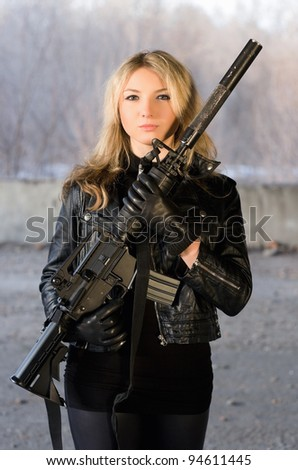 Armed beautiful young woman with a rifle in neglected house - stock photo