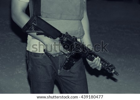 Armed man hands carrying a rifle in a battlefield, night vision portrait, war concept