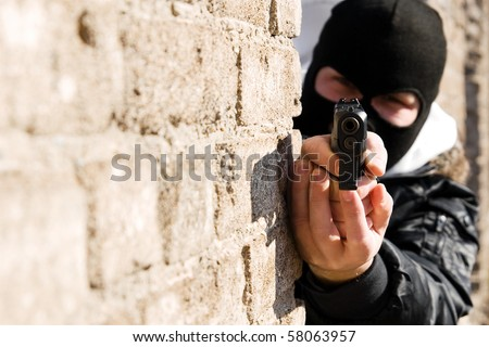 Armed man in black mask pointing a gun in camera - stock photo