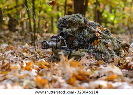 Armed man in camouflage lying on the leaves in the forest with rifle/Sniper lies among the fallen leaves in forest - stock photo