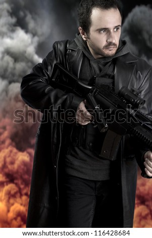 Armed man on background with explosion of fire and smoke - stock photo