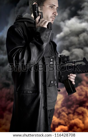 Armed man on background with explosion of fire and smoke, police - stock photo