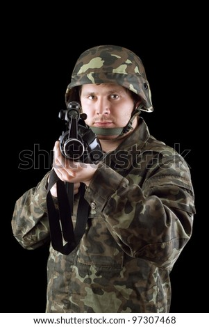 Armed man pointing a rifle in studio - stock photo
