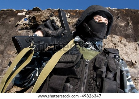 Armed officer in full ammunition holding rifle on his shoulder - stock photo