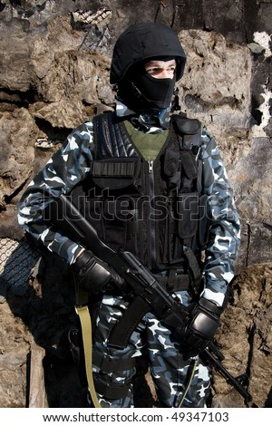 Armed officer in full ammunition with automatic russian rifle AK47 - stock photo