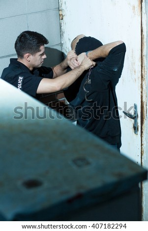 Armed policeman is arresting dangerous masked kidnapper - stock photo