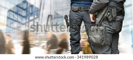 Armed policemen on guard in busy street with modern glass buildings and people walking - stock photo