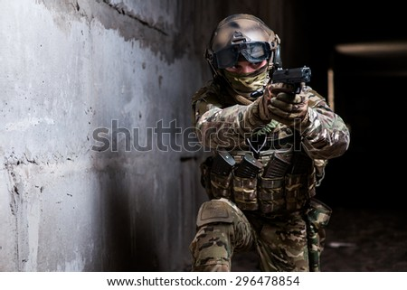 Armed ranger in camouflage,mask and helmet aiming his gun in the dark room/Armed ranger in camouflage,mask and helmet aiming his gun in the dark room - stock photo