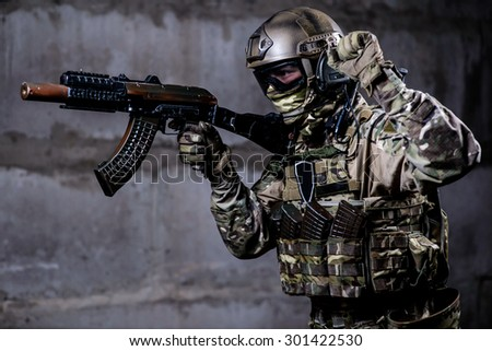Armed ranger in camouflage,mask and helmet shows special signal during a special military operation in the building/Armed ranger in camouflage,mask and helmet shows special signal - stock photo