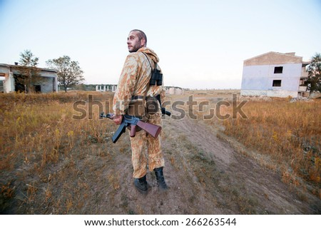 Armed rebellion with the Kalashnikov on the ruined city background - stock photo