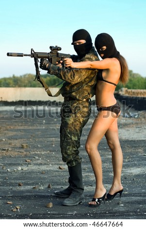 Armed soldier and pretty woman in black masks - stock photo