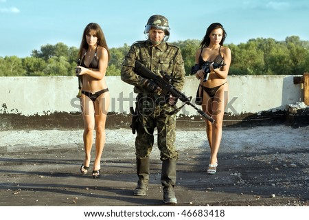 Armed soldier and two women with rifles