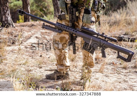 Armed soldier holding large caliber sniper rifle during military training in forest - stock photo