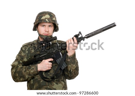 Armed soldier holding m16 in studio. Isolated