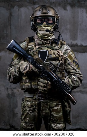 Armed soldier in camouflage, mask,helmet with rifle in hands looking at the camera - stock photo