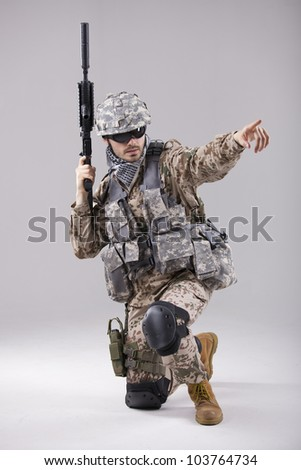 Armed Soldier in camouflage pointing with a finger - stock photo