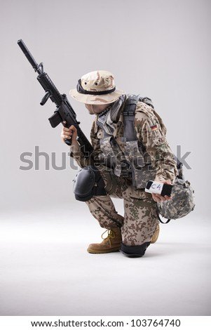 Armed Soldier in camouflage with explosive in his hand - shot in white studio - stock photo