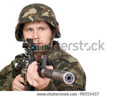 Armed soldier pointing m16 in studio. Isolated