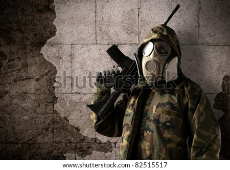 armed soldier with gas mask wearing a camouflage uniform against a wall