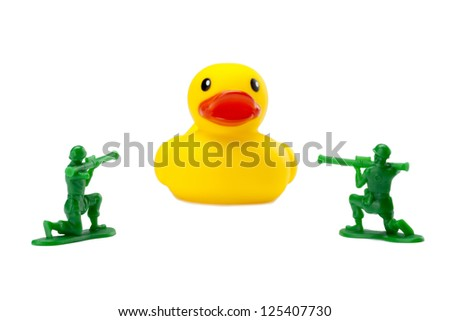 Armed soldiers aiming at a giant rubber duck - stock photo