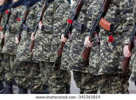Armed Soldiers in Camouflage Uniforms with Red Carnations and Automatic Weapons. - stock photo