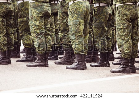 Armed Soldiers legs in green Camouflage Military Uniform - stock photo
