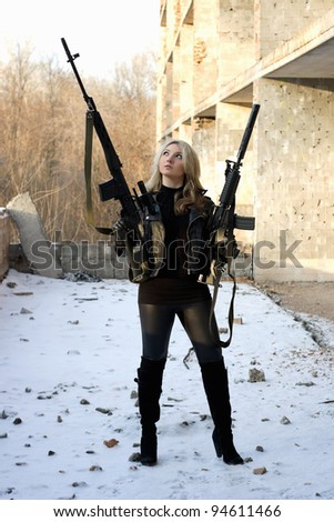 Armed strong girl outside the building - stock photo