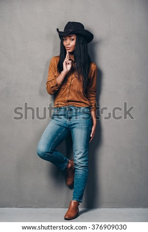 Armed with her beauty. Full length of beautiful young African woman in hat gesturing handgun and looking at camera while standing against grey background - stock photo