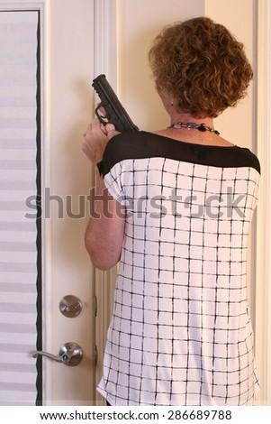 Armed woman with semi-automatic in home invasion scenario - stock photo