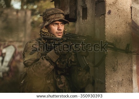 Armed young soldier participating in military manoeuvres