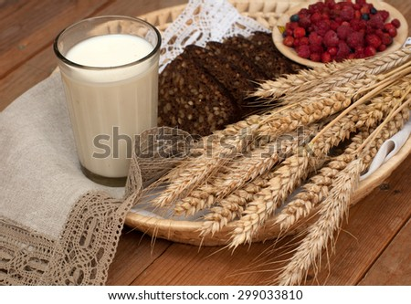 Armful of ears, fresh bread, raspberries and a glass of milk on a straw tray with a linen napkin