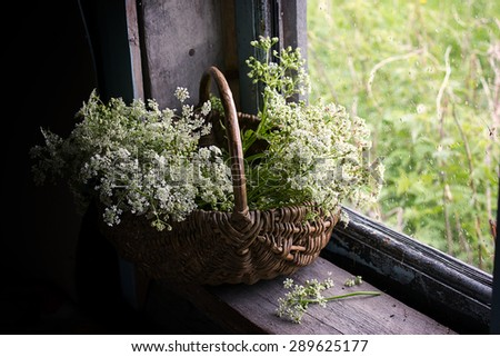 Armfuls of white wildflowers in a basket on an old window sill.