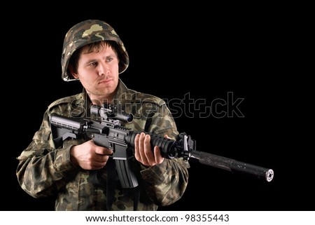 Arming soldier and a rifle in studio. Isolated