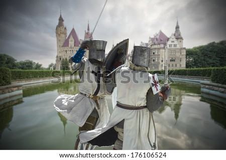 Armored fighting knights with medieval castle in the background, Moszna, Poland - stock photo