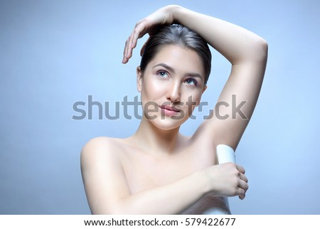 armpit axillary space attractive young caucasian woman  body care isolated  on blue background studio shot figure body applying deodorant