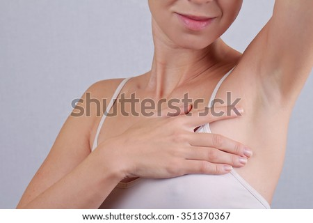 Armpit epilation, laser hair removal. Young woman holding her arms up and showing underarms, armpit, ideal smooth clear skin
