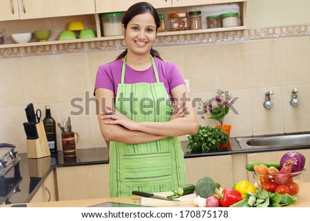 Arms crossed smiling young woman in her kitchen - stock photo