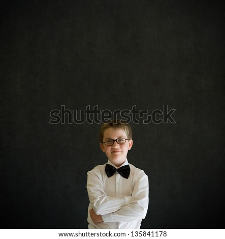 Arms folded boy dressed up as business man, teacher or student on blackboard background - stock photo