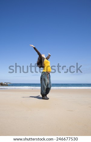 arms up pregnant woman with yellow shirt at Asturian beach - stock photo