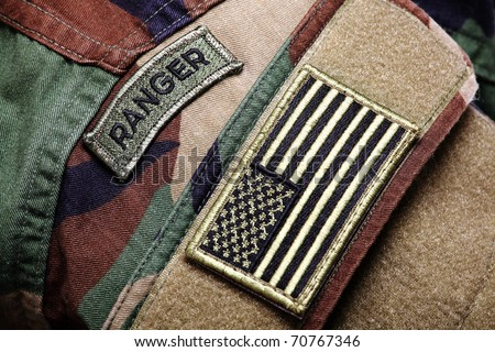 Army BDU (woodland camo uniform) with ranger patch and US flag. - stock photo