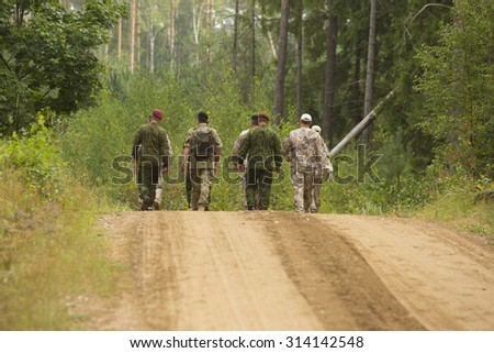 Army exercise: Military person going by road - stock photo