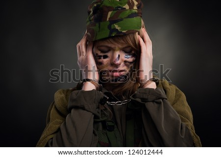 army girl cover ears with hands in handcuffs closed eyes, soldier woman in a military uniform over black background - stock photo