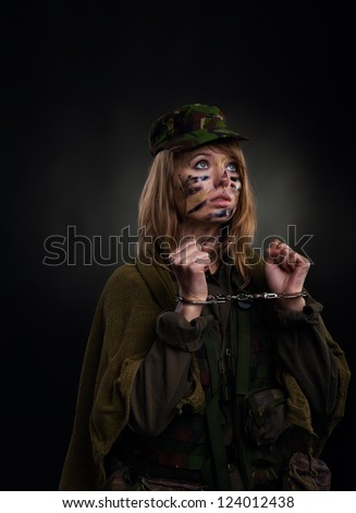 army girl in handcuffs, soldier woman in a military uniform over black background - stock photo