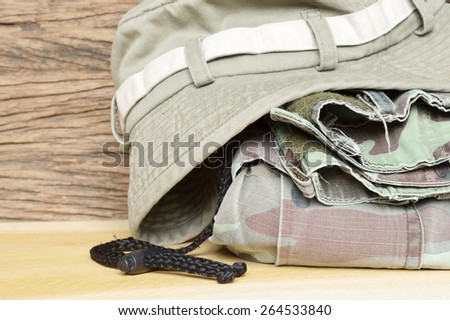 army pants and hat on wooden background - stock photo