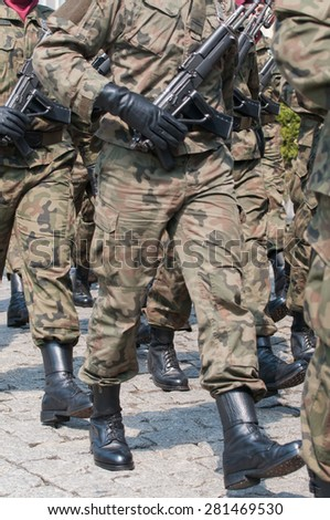 Army parade - armed soldiers in camouflage military uniform are marching