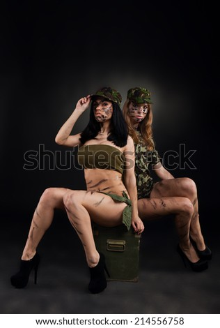 army sexy girls, two long legs soldier woman sitting on ammunition box wear military camouflage uniform cap full length over black background