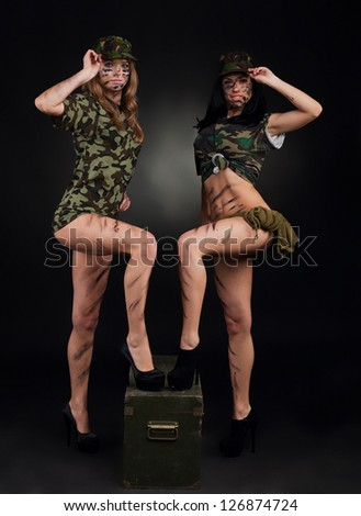 army sexy girls, two long legs soldier woman standing on ammunition box wear military camouflage uniform cap full length over black background